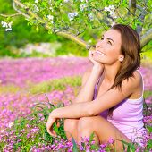Closeup portrait of dreamy woman spending time in blooming park, watching for first blossom of natur