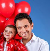 Closeup portrait of happy young father with little child over blue sky background, playing with red