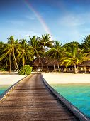 Wooden bridge to island beach resort, beautiful colorful rainbow over fresh green palm trees, luxury