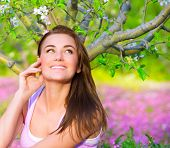 Closeup portrait of happy woman in blooming garden, having fun outdoors, sitting down on pink floral