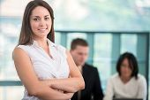 Smiling business woman with arms crossed posing in office