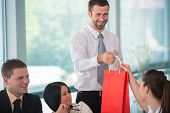 Smiling business man handing gift to female colleague