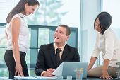 Smiling businessman working with female colleagues in office