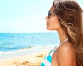 Beautiful Woman Wearing Sunglasses over Sea Background. Beauty Sexy Girl Relaxed on the Beach, Summe