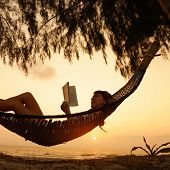 Lady relaxing in the hammock with book