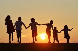 stock photo of jumping  - Happy children silhouettes on summer meadow running and jumping - JPG