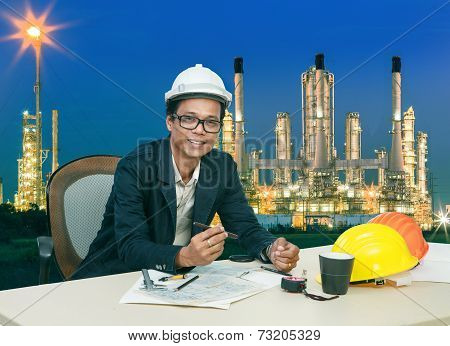 Engineering Man Working On Table Aginst Beautifult Lighting Of Oil Refinery Plant