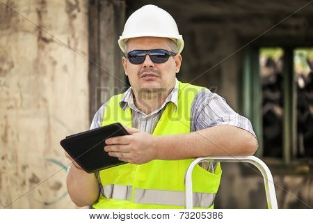 Building inspector with tablet near collapsed building