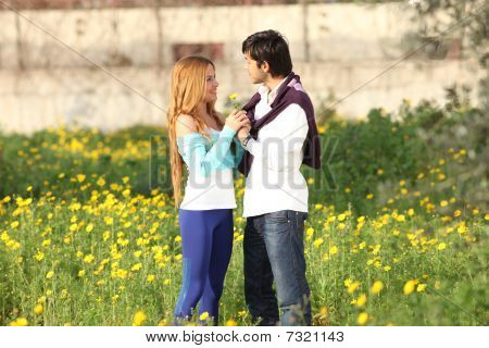 Young Couple Standing In Meadow