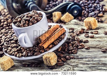 Spilled coffee beans in coffee cup on a very old wooden table with cane sugar. In the background an
