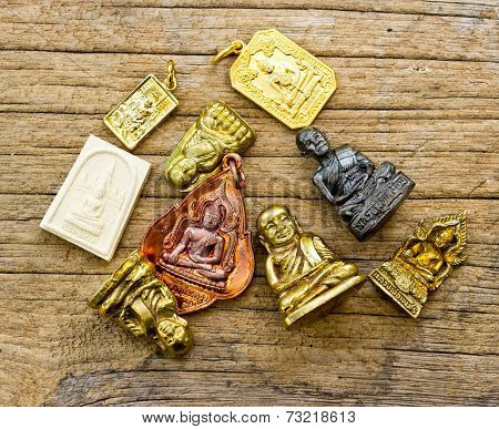 Many Small Buddha Image Used As Amulets On Wood Background