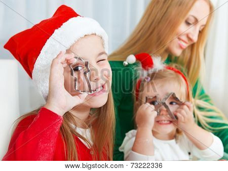 Two Little Girls With Mother Baking Christmas Cookies