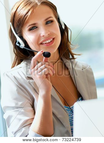 businesswoman talking on the phone while working on her compute