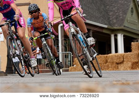 Low-angle View Of Female Cyclists Leaning Into Turn