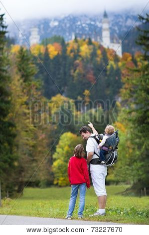 Young Father Showing His Two Kids  The Neuschwanstein Castle in Germany in autumn