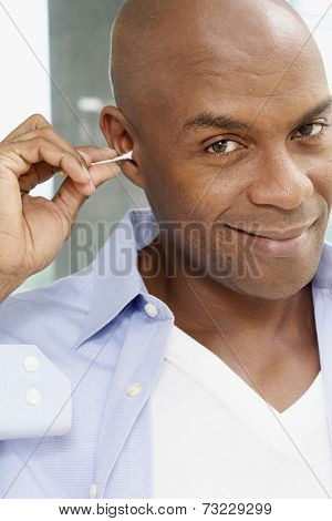 African American man cleaning ear with cotton swab