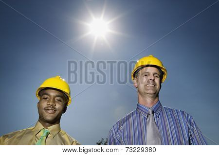 Multi-ethnic businessmen wearing hard hats
