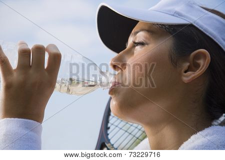 Hispanic woman drinking from water bottle