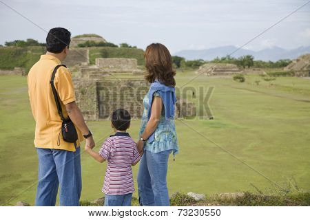 Hispanic family looking at ruins, Oaxaca, Mexico