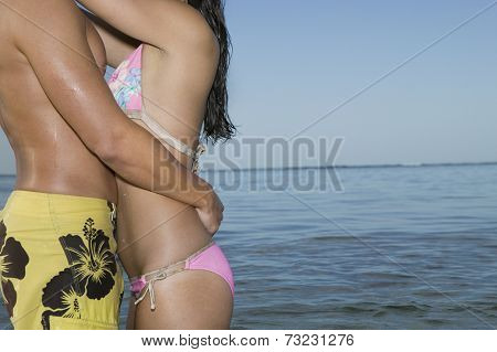 Multi-ethnic couple in bathing suits hugging