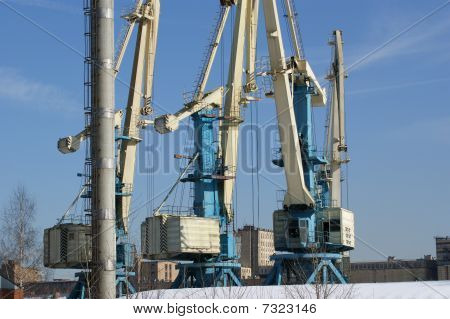 Cargo Cranes Against A Background Of Blue Sky