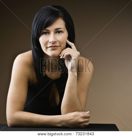 Hispanic woman resting elbow on table