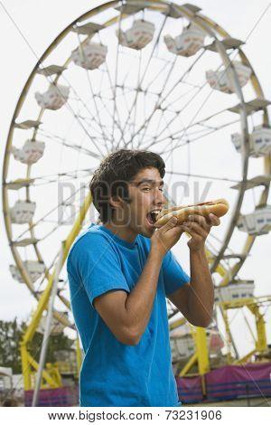 Mixed Race teenaged boy eating hot dog at carnival