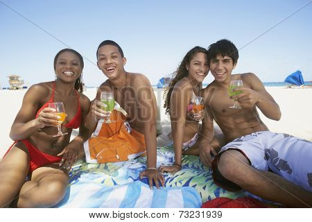 Hispanic couples holding drinks at beach