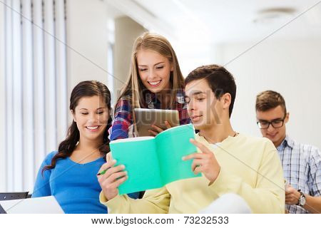 education, high school, teamwork and people concept - group of smiling students with tablet pc computer and notebooks sitting in lecture hall