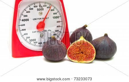 Figs And Kitchen Scales Close Up On A White Background