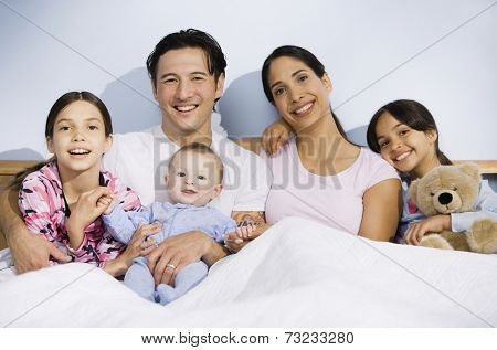 Multi-ethnic family sitting in bed
