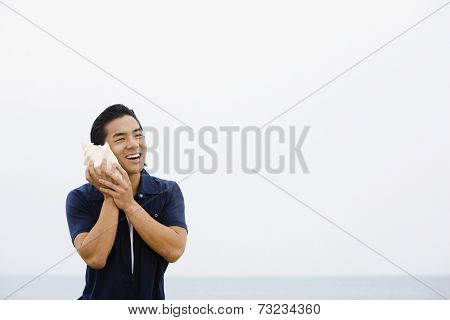 Asian man listening to conch shell