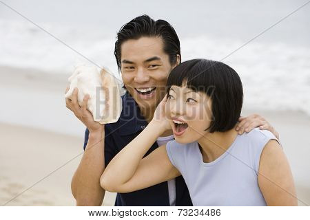 Asian couple holding conch shell