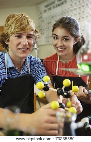 Male and female teenagers in science class