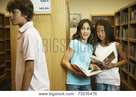 Multi-ethnic girls looking at boy in library