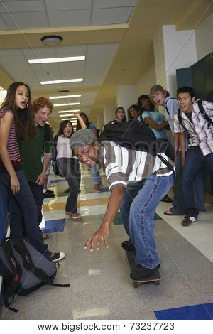 African American teenaged boy riding skateboard in school hallway