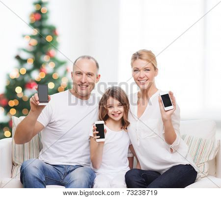 family, holidays, technology and people - smiling mother, father and little girl with smartphones over living room and christmas tree background