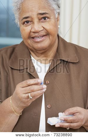 Senior African American woman holding medication