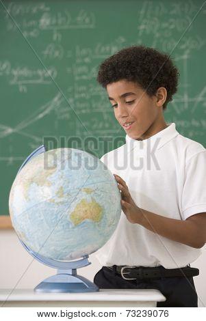 Hispanic boy looking at classroom globe