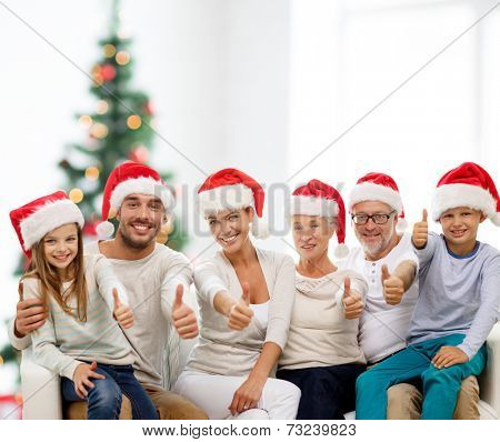 family, generation, gesture, holidays and people concept - happy family in santa helper hats showing thumbs up over living room and christmas tree lights background