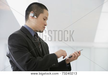 Asian businessman talking on hands-free device
