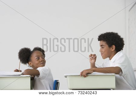Hispanic boy blowing spitball on girl in class
