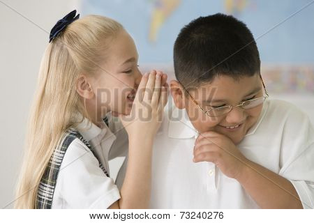 Multi-ethnic children telling secret