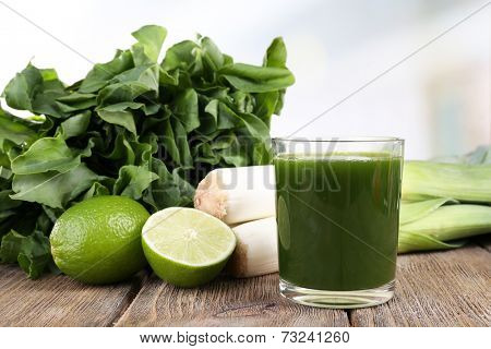 Tuft of sorrel, glass of fresh vegetable juice, spring onion and lime on wooden table