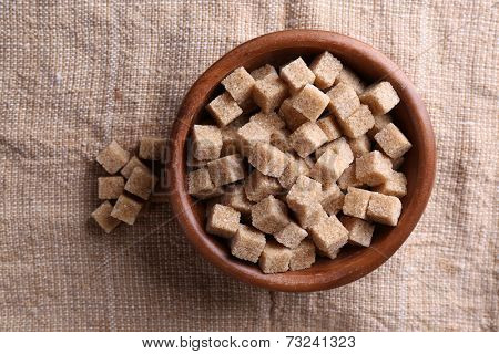 Brown sugar cubes in bowl on sackcloth background
