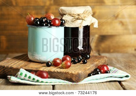 Ripe blackcurrants and gooseberries in mug and glass jar with tasty jam on board, on wooden background.