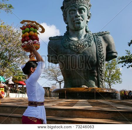 BALI, INDONESIA - SEPTEMBER 19, 2014: A devotee carries a fruit basket as offerings to Lord Vishnu at the Garuda Wisnu Kencana at Uluwatu, Bali Island.