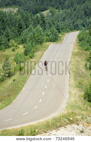 a man skiing with roller ski on a mountain road, Serbia