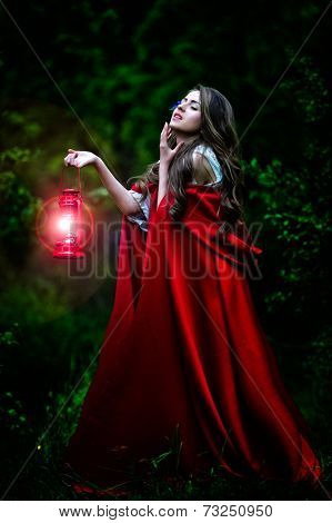 beautiful woman with red cloak and lantern in the woods by night