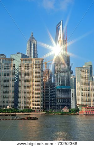 Shanghai urban architecture and skyline with sun light reflection over river